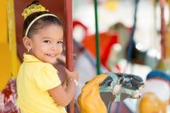 Leuk gemengd rasmeisje die een carrousel berijden Stock Afbeeldingen