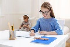 Leuk gemotiveerd meisje die een ijverige student zijn stock afbeeldingen