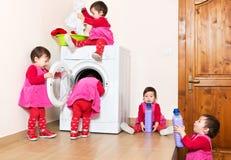 Leuk glimlachen weinig kind die wasmachine thuis met behulp van stock afbeelding