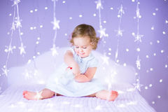 Leuk glimlachend babymeisje op bed tussen mooie purpere lichten Royalty-vrije Stock Afbeeldingen