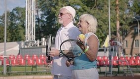 Leuk glimlachend rijp paar voor het worden klaar om tennis op de tennisbaan te spelen Actieve vrije tijd in openlucht Hogere mens stock footage