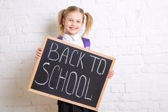 Leuk glimlachend schoolmeisje in eenvormige status met bord en het glimlachen Terug naar School Stock Afbeelding