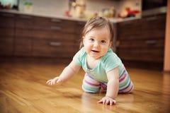 Leuk glimlachend weinig zitting van het babymeisje op het bed met zacht speelgoed Royalty-vrije Stock Foto's