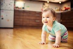 Leuk glimlachend weinig zitting van het babymeisje op het bed met zacht speelgoed Royalty-vrije Stock Afbeeldingen