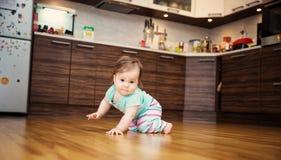 Leuk glimlachend weinig zitting van het babymeisje op het bed met zacht speelgoed Stock Foto