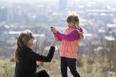 Leuk grappig klein glimlachend blond meisje in roze kledingsholding en Royalty-vrije Stock Foto's