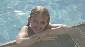 Leuk grappig meisje die in gele zonnebril in de camera kijken die, kijkend uit de pool, die op de rand houden glimlachen stock videobeelden