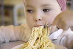 Leuk grappig meisje die spaghetti thuis eten Stock Foto's