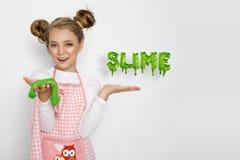 Leuk grappig meisje met slijm in de keuken Het meisje kookt en bakt haar muffins, maakt een cake en een slijm stock fotografie