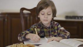 Leuk grappig weinig jongen in geruit overhemd die zijn thuiswerkzitting doen thuis bij de lijst De schooljongentekening in van he stock video