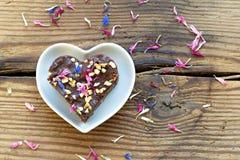 Leuk hart gestalte gegeven die stuk van chocoladecake met bloemen wordt bestrooid Stock Foto