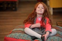 Leuk het glimlachen meisjeholding lip-vormig stuk speelgoed met hart royalty-vrije stock afbeeldingen