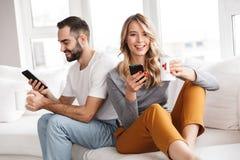 Leuk houdend van paar die binnen thuis mobiele telefoons met behulp van royalty-vrije stock foto's