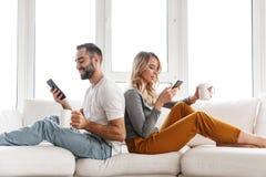 Leuk houdend van paar die binnen thuis mobiele telefoons met behulp van stock foto