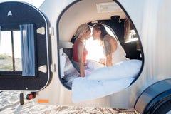 Leuk houdend van paar die goede ontwaken in compacte aanhangwagen samen voelen royalty-vrije stock foto's