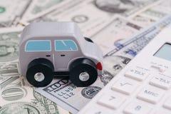 Leuk houten klein stuk speelgoed autoparkeren naast witte calculator op stapel van geld, de auto, de huur of de verzekering die v royalty-vrije stock afbeeldingen