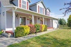 Leuk huis buiten met rode blinden op een de zomerdag stock afbeeldingen