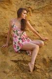 Leuk jong donkerbruin meisje in kleding door het zand Stock Foto