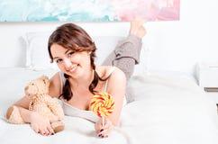 Leuk jong donkerbruin meisje met twee vlechten thuis pyjama's liggend o Stock Afbeelding