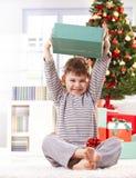 Leuk jong geitje dat de hoogte van de Kerstmisgift opheft stock foto's