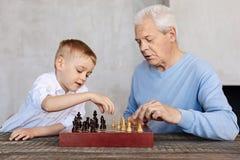 Leuk jong geitje en zijn grootouder het spelen schaak stock fotografie