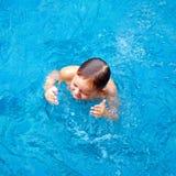 Leuk jong geitje, jongen die in poolwater ploeteren, hoogste mening Royalty-vrije Stock Afbeelding