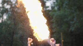 Leuk jong gunstmeisje die een show met vlam uitvoeren die zich voor het bos Bekwame fireshowkunstenaar uitademen bevinden stock video