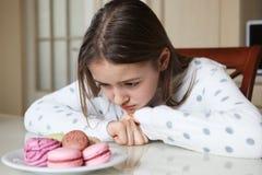 Leuk jong meisje die droevig makarons bekijken en zefir stock foto