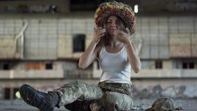 Leuk jong meisje die een mooie kroon van tarwe op haar hoofd, het glimlachen zitting op de vloer in stoffige verlaten vuil zetten stock video