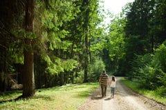 Leuk jong meisje die langs in een bos met haar vader op mooie de zomerdag wandelen royalty-vrije stock afbeeldingen
