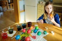 Leuk jong meisje die paaseieren thuis verven Kind die kleurrijke eieren voor Pasen-jacht schilderen Jong geitje die klaar voor Pa royalty-vrije stock foto's