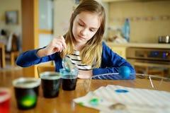 Leuk jong meisje die paaseieren thuis verven Kind die kleurrijke eieren voor Pasen-jacht schilderen Jong geitje die klaar voor Pa stock afbeeldingen