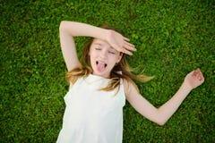 Leuk jong meisje die pret op een gras op de binnenplaats op zonnige de zomeravond hebben stock afbeelding