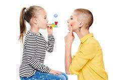 Leuk jong meisje met toespraaktherapeut die speciale oefeningen maken op logopediekantoor Het concept van de kindlogopedie op wit stock foto