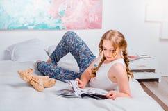 Leuk jong meisje met twee vlechten, thuis dragend pyjama's, het liggen Stock Foto's