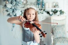 Leuk jong meisje met violinl in de ruimte van de Kerstmisdecoratie Jonge meisje het spelen viool bij Kerstboom Stock Afbeelding