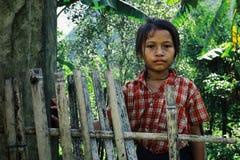leuk jong meisje naast een bamboeomheining in een aardig rood overhemd royalty-vrije stock fotografie