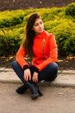 Leuk jong meisje in oranje jasje Stock Afbeeldingen