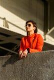 Leuk jong meisje in oranje jasje Stock Afbeelding