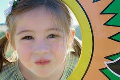 Leuk jong meisje in paardestaarten, die camera, binnen - tussen een kleurrijk kader bekijken Stock Fotografie