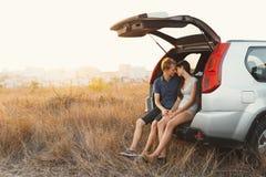 Leuk jong paar in liefdezitting in een auto met een open boomstam HU royalty-vrije stock foto's