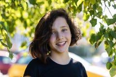 Leuk jong tienermeisje die zich onder die een lindeboom bevinden door bladeren wordt omringd stock foto's
