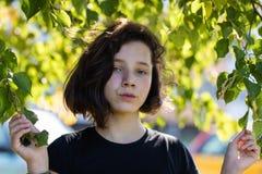 Leuk jong tienermeisje die zich onder die een lindeboom bevinden door bladeren wordt omringd stock foto