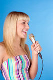 Leuk jong vrouwelijk het zingen lied, dat over blauw wordt geïsoleerdd Stock Fotografie