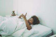 Leuk jong zwart meisje in bed met smartphone Royalty-vrije Stock Foto