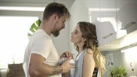 Leuk Kaukasisch paar die in de keuken flirten stock videobeelden