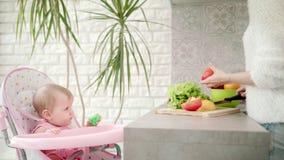 Leuk kind die op moeder kokend voedsel kijken Vrouwelijke kokende groenten stock video