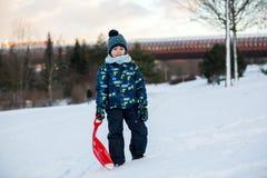 Leuk kind, jongen, die met loodje in de sneeuw glijden, wintertijd stock foto's