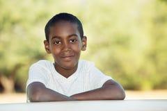 Leuk kind met gevouwen wapens bij lijst Stock Fotografie
