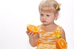 Leuk kind met twee sinaasappelen in haar hand stock foto